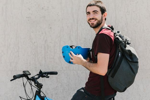 Homem sorridente, segurando, capacete, ligado, bicicleta