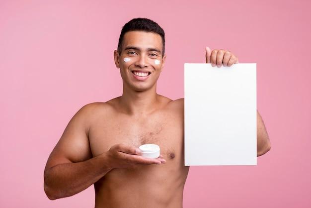 Homem sorridente segurando creme facial e um cartaz em branco