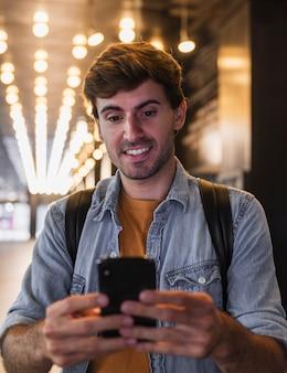 Homem sorridente segurando e olhando para celular