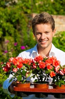 Homem sorridente segurando flores em vasos