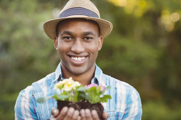 Homem sorridente segurando flores no jardim