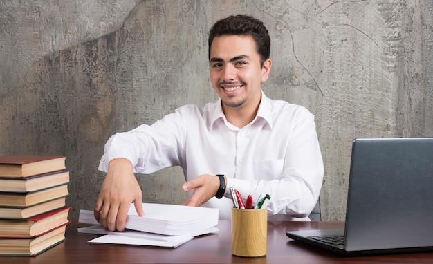 Homem sorridente segurando folhas de papel e sentado à mesa. foto de alta qualidade
