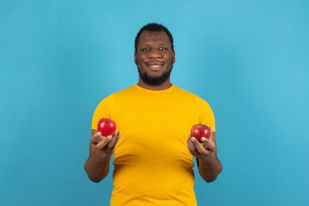 Homem sorridente segurando maçãs com as duas mãos, fica sobre a parede azul.