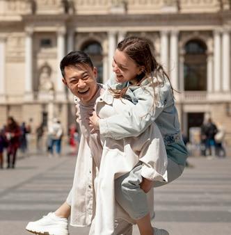 Homem sorridente segurando mulher nas costas
