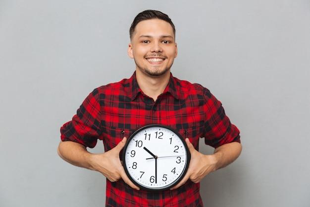 Homem sorridente segurando o relógio nas mãos