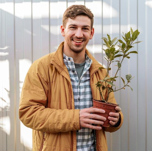 Homem sorridente segurando o vaso com uma pequena árvore