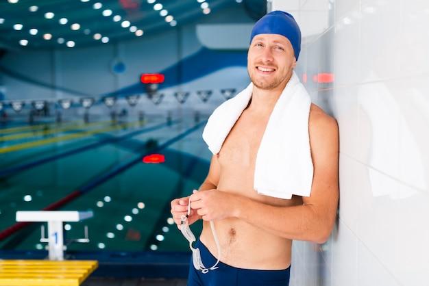 Homem sorridente segurando óculos de natação