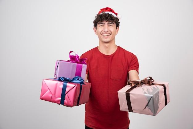 Homem sorridente segurando seus presentes de natal.