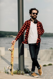 Homem sorridente, segurando, skateboard