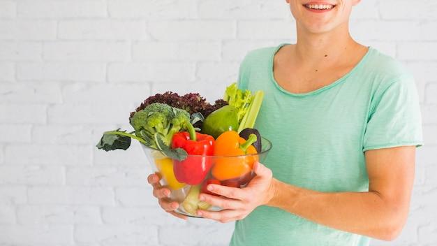 Homem sorridente, segurando, tigela, de, fresco, orgânica, legumes