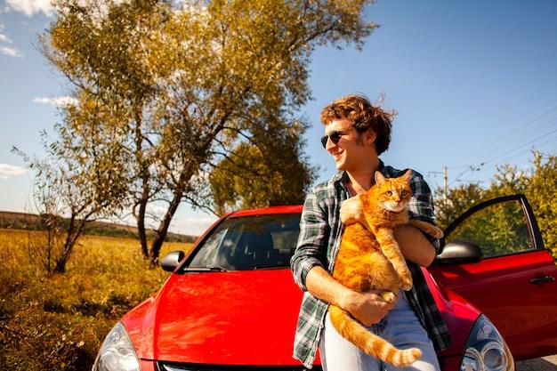 Homem sorridente segurando um gato na frente de um carro