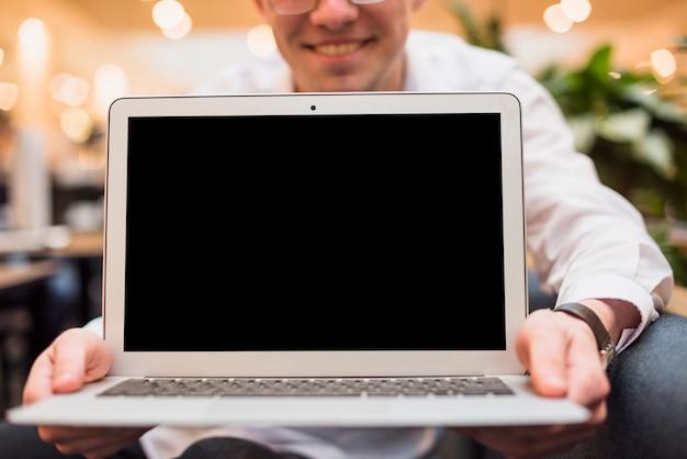 Homem sorridente segurando um laptop aberto com tela preta