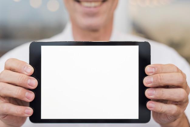 Homem sorridente segurando um tablet vazio