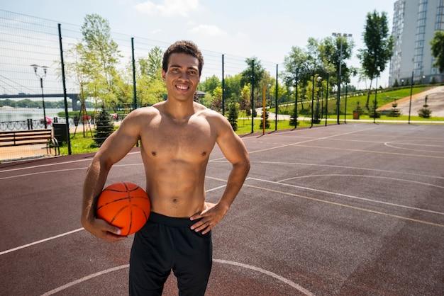 Homem sorridente segurando uma bola em um parque urbano