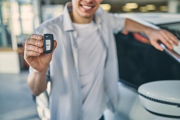 Homem sorridente segurando uma chave atrás de um carro no showroom