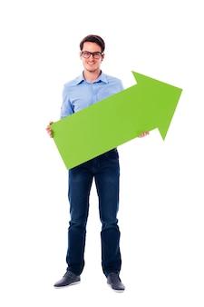 Homem sorridente segurando uma seta verde