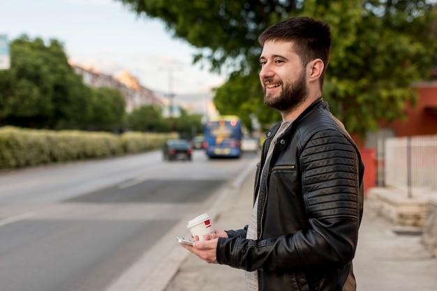 Homem sorridente segurando xícara e smartphone
