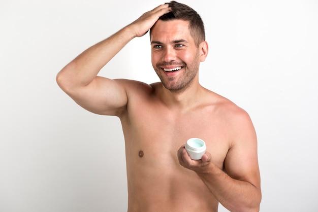 Homem sorridente sem camisa, aplicando cera no cabelo dele contra o pano de fundo branco