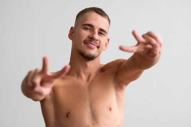 Homem sorridente sem camisa posando enquanto faz os sinais da paz
