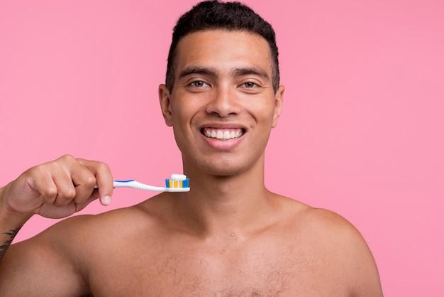 Homem sorridente sem camisa segurando uma escova de dentes