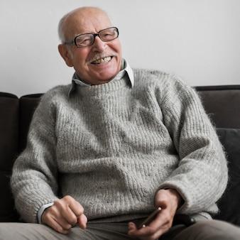 Homem sorridente sênior em uma casa de repouso segurando um smartphone