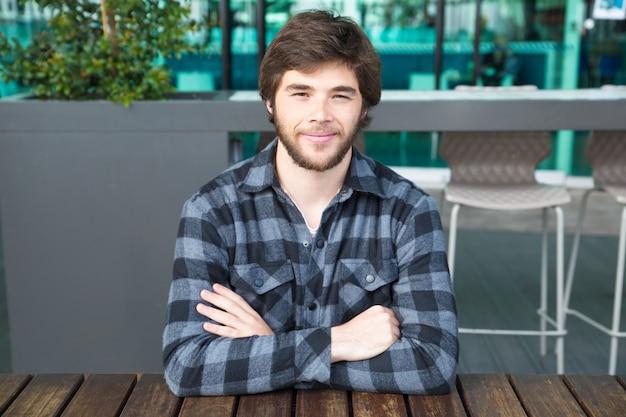 Homem sorridente, sentado à mesa de café de rua com os braços cruzados