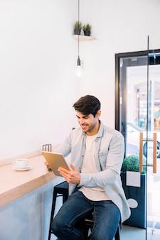 Homem sorridente sentado e trabalhando em tablet