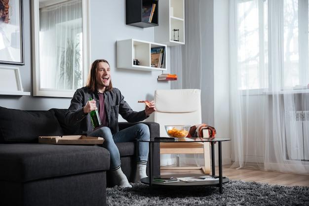 Homem sorridente, sentado em casa dentro de casa, comendo pizza.