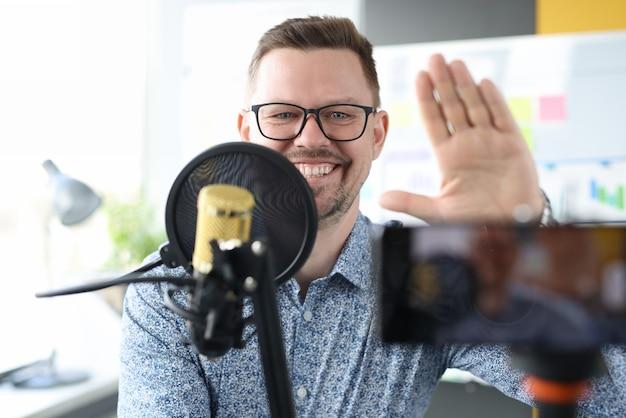 Homem sorridente sentado em frente a um microfone e acenando para a câmera com a mão