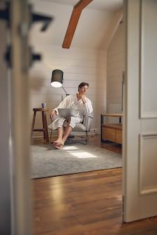 Homem sorridente sentado na cadeira em um quarto moderno de sua casa