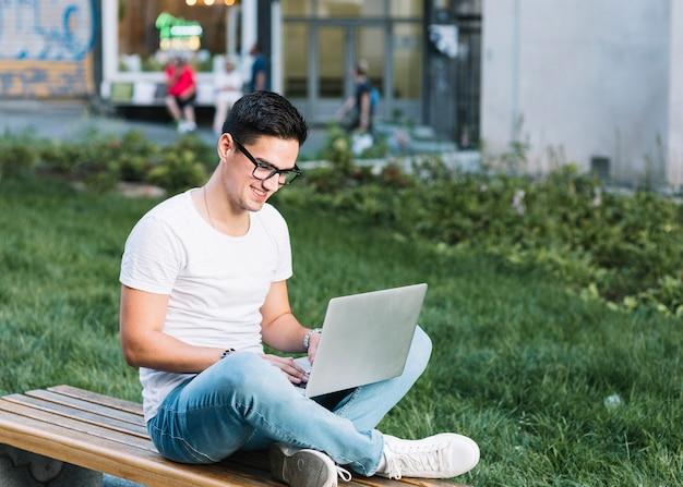 Homem sorridente, sentado no banco, trabalhando no laptop