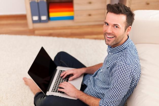 Homem sorridente sentado no chão com um laptop