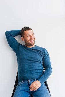 Homem sorridente, sentado no chiar em casa