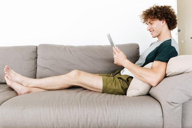 Homem sorridente, sentado no sofá, usando computador tablet