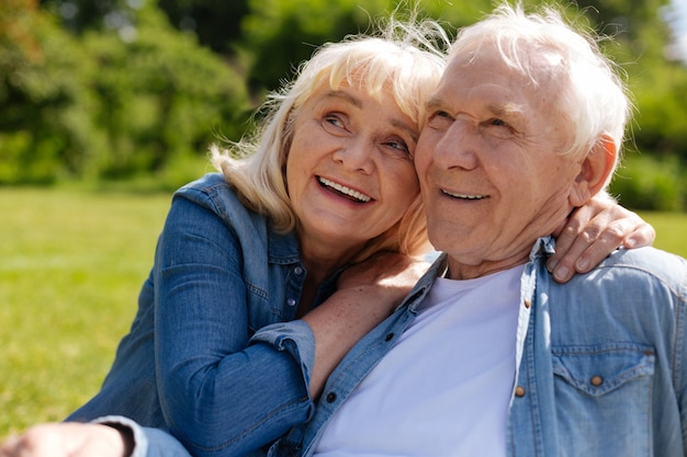Homem sorridente sentado perto de sua esposa sentindo felicidade enquanto olha em uma direção
