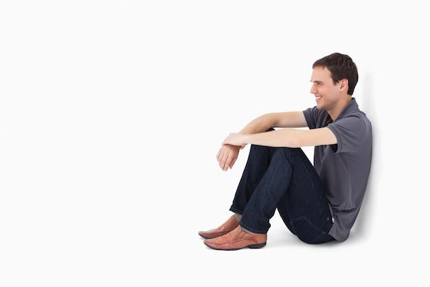 Homem sorridente, sentando, contra, um, parede