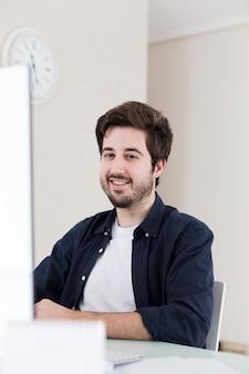 Homem sorridente, sentando, em, escritório