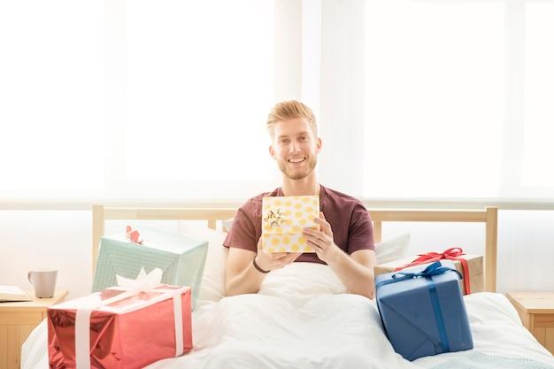 Homem sorridente, sentar-se cama, segurando, presentes