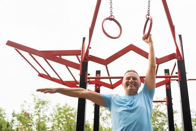 Homem sorridente sorridente fazendo exercícios ao ar livre