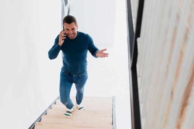 Homem sorridente subindo escadas e falando no telefone