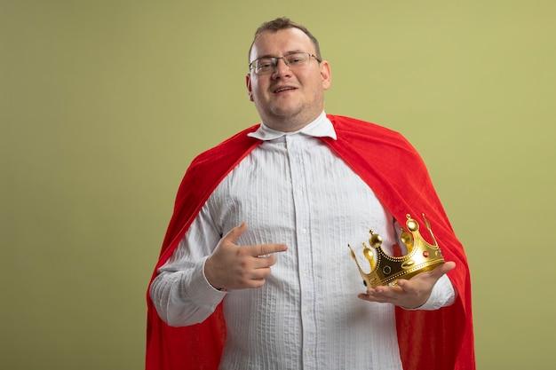 Homem sorridente super-herói eslavo adulto com capa vermelha usando óculos e coroa apontando para a coroa isolada na parede verde oliva com espaço de cópia