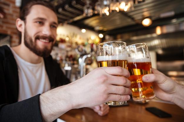 Homem sorridente, tilintar de copos com amigo no bar