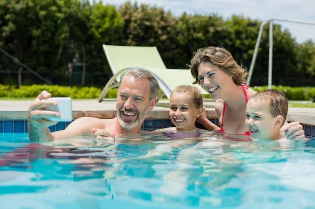Homem sorridente tirando uma selfie com a família na piscina