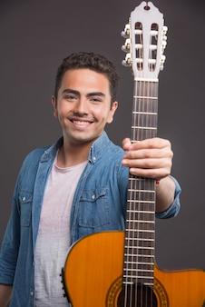 Homem sorridente tocando guitarra em fundo escuro. foto de alta qualidade