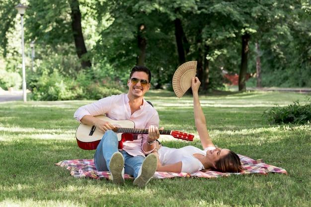 Homem sorridente tocando violão no parque