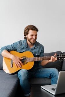 Homem sorridente tocando violão
