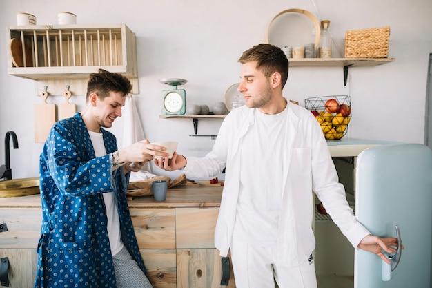 Homem sorridente tomando tigela de seu amigo na cozinha