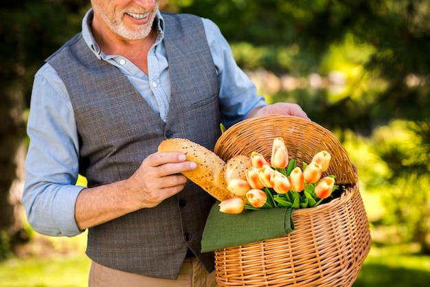 Homem sorridente tomando uma baguete da cesta de piquenique