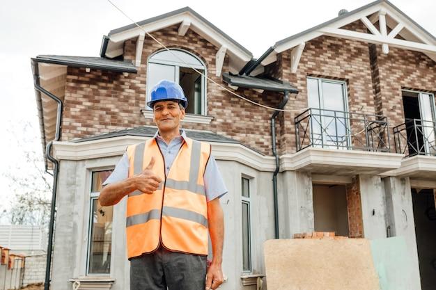 Homem sorridente trabalhador asiático construtor ou engenheiro civil com capacete de segurança e colete reflexivo aparecendo o polegar na casa particular do canteiro de obras