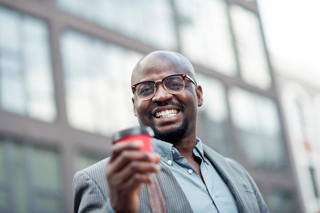 Homem sorridente. trabalhador de escritório afro-americano barbudo de óculos, sorrindo e bebendo café